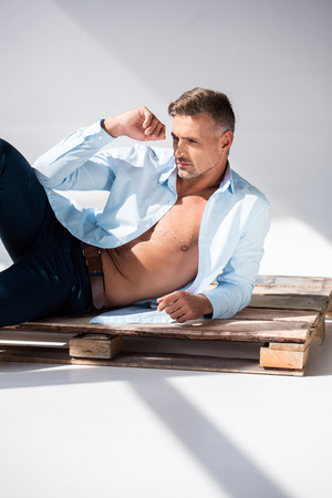 Attractive adult man with unbuttoned shirt lying on wooden pallet on white background and looking away