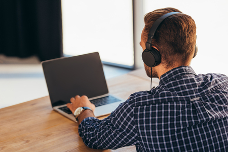 Partial view of man in headphones taking part in webinar at tabletop with notebook in office Stock Photo