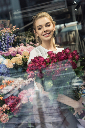 View through window of attractive florist holding bouquet of burgundy roses in flower shop and looking at camera Zdjęcie Seryjne