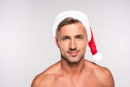 Handsome shirtless man in Santa hat smiling at camera isolated on grey background