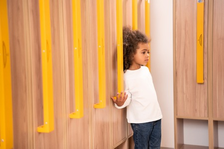 Adorable African American kid standing near wooden lockers in kindergarten cloakroom Stock Photo - 110357443