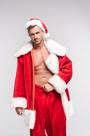 Sexy muscular man in Santa costume looking at camera isolated on grey background Stock Photo