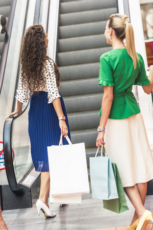 Back view of young women with paper bags walking at escalator in shopping mall