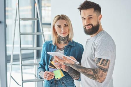 Pareja joven tatuada con tableta digital y sonriendo a la cámara en casa nueva