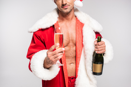 Cropped shot of sexy Santa holding glass of champagne and bottle isolated on grey background Stock Photo
