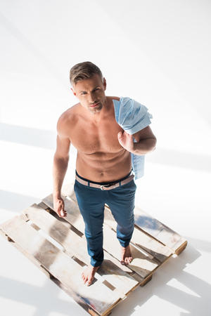 High angle view of shirtless handsome adult man standing on pallet on white background and looking at camera Stock fotó