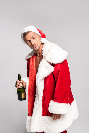 Handsome man in Santa costume holding bottle of champagne and looking away isolated on grey background