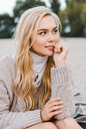 Attractive smiling blonde girl in autumn outfit sitting on beach, touching lips and looking away