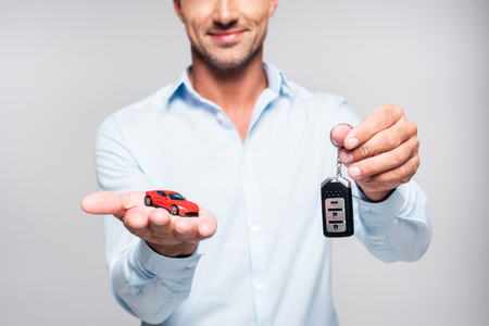 Cropped shot of smiling adult man holding car alarm remote and toy red car isolated on white background