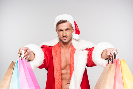 Handsome man in Santa costume holding shopping bags and smiling at camera isolated on grey background