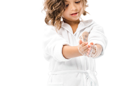 Little kid in bathrobe washing hands with soap isolated on white background