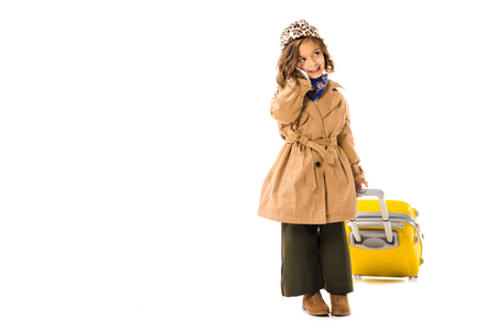 Happy little child in trench coat with yellow suitcase talking by phone isolated on white background