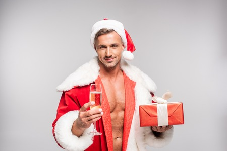 Smiling sexy Santa holding glass of champagne and gift box isolated on grey background 스톡 콘텐츠