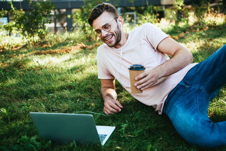 Cheerful handsome man taking part in webinar and lying on grass in park