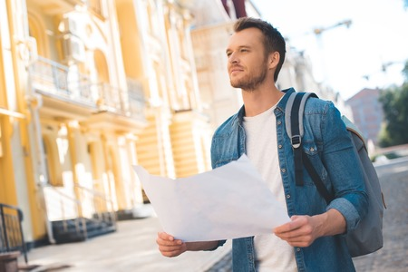 Handsome young tourist with backpack and map looking up on street