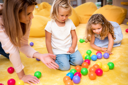 Educator pointing on colored balls to kids in kindergarten