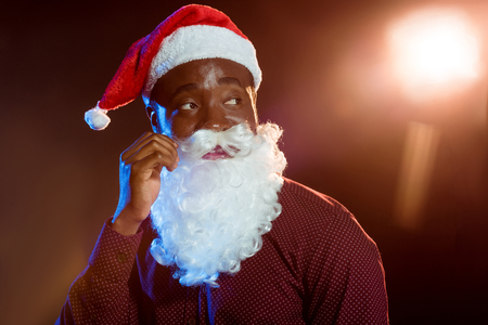 African American man adjusting Santa beard on black with backlit Stock Photo