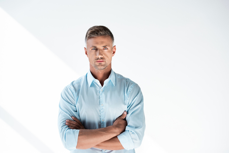 Serious adult man in shirt looking at camera with crossed arms isolated on white background Banco de Imagens