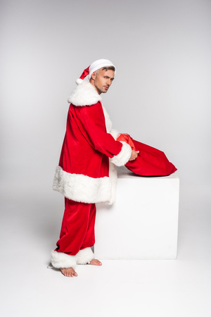 Handsome barefoot man in Santa costume holding red bag and looking at camera on grey background