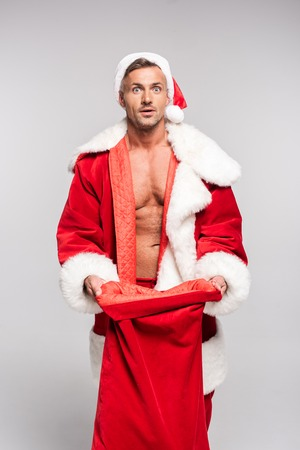 Shocked man in Santa costume opening red bag and looking at camera isolated on grey background