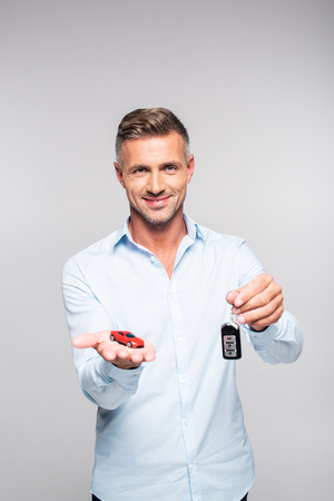 Smiling adult man holding car alarm remote and toy red car isolated on white background