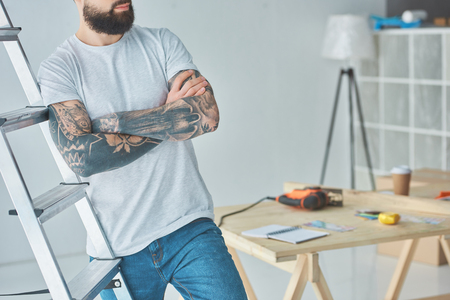 Cropped shot of bearded tattooed man standing with crossed arms near stepladder Reklamní fotografie