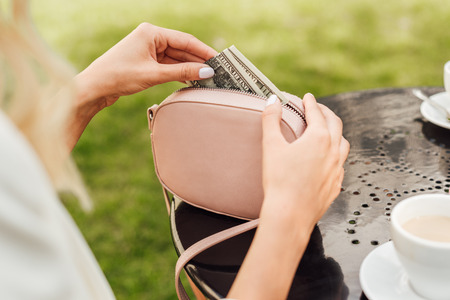 Cropped image of woman taking cash from handbag at table in cafe Stock Photo
