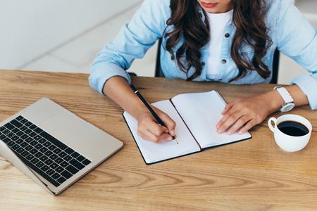 Vista parziale della donna che prende appunti mentre partecipa al webinar in ufficio