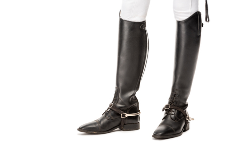 Cropped shot of horsewoman standing in leather boots isolated on white background