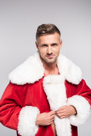 Portrait of handsome man in Santa costume smiling at camera isolated on grey background