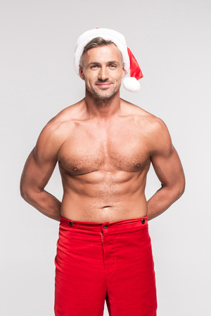 Portrait of handsome shirtless man in Santa hat smiling at camera isolated on grey background