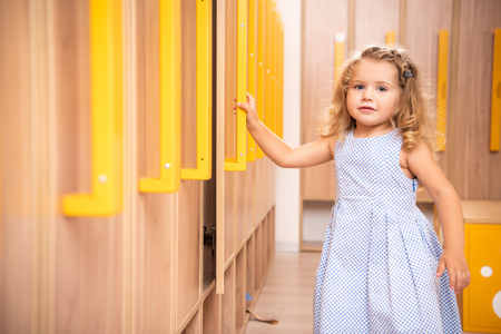 Smiling adorable kid opening locker in kindergarten cloakroom and looking at camera