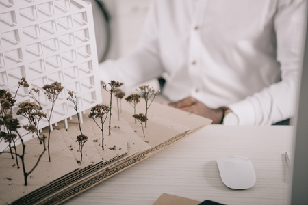 Cropped image of African American architect sitting near architecture model on tabletop in office