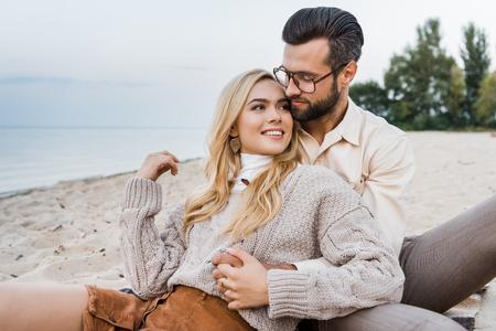 Sonriente novia y novio en traje de otoño sentado y abrazándose en la playa
