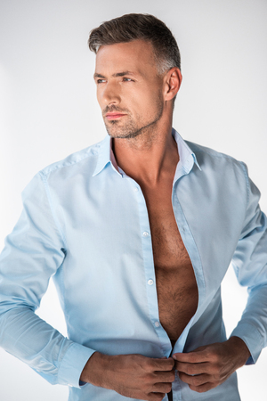 Handsome adult man buttoning shirt and looking away isolated on white background Stock Photo