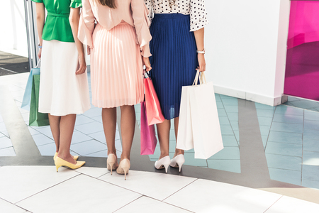 Low section of young women holding paper bags and standing together in shopping mall