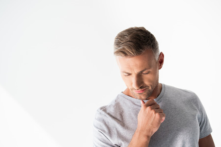 Thoughtful adult man in blank grey t-shirt touching his chin and looking down isolated on white background