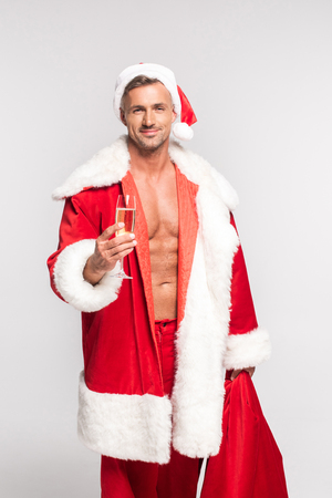 Handsome sexy Santa holding glass of champagne and smiling at camera isolated on grey background