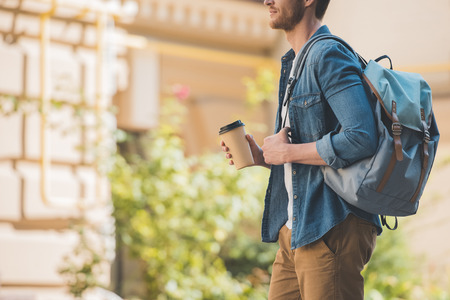 Cropped shot of attractive young man with coffee to go and backpack walking by city