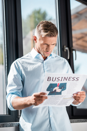 Serious adult businessman reading business newspaper in front of window 版權商用圖片