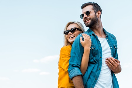 Low angle view of smiling girlfriend hugging boyfriend against blue sky background Фото со стока