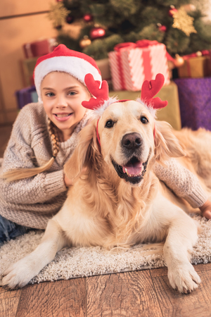 Smiling child in Santa hat and golden retriever dog with deer horns lying near Christmas presents