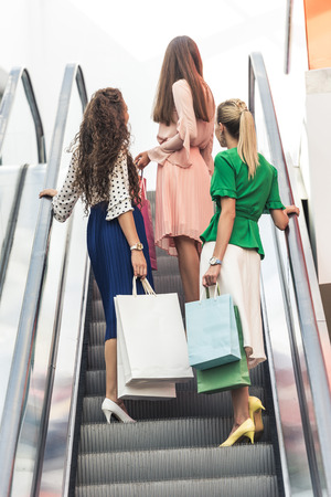 Low angle view of stylish girls holding shopping bags on escalator Banco de Imagens