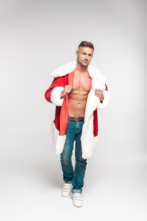 Handsome muscular man wearing Santa costume and looking at camera on grey background