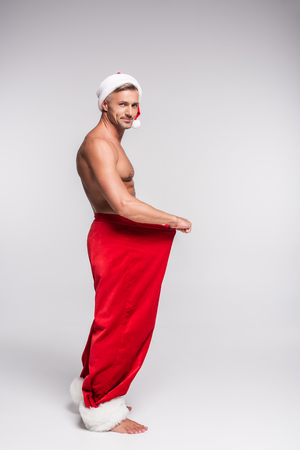 Side view of shirtless man in Santa hat holding red pants and smiling at camera on grey background Stock Photo