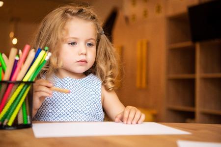 Adorable child holding felt pen for drawing in kindergarten, pen holder with felt tip pens on tabletop