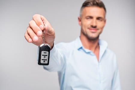 Close-up shot of smiling adult man holding car alarm remote isolated on white background Banco de Imagens