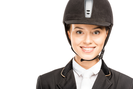 Close-up portrait of happy young horsewoman in helmet looking at camera isolated on white background Banco de Imagens