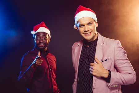 fc929104a1155 African American man in Santa hat pointing at camera while his friend in  pink jacket posing