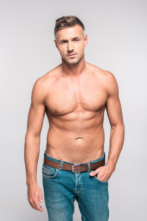 Portrait of handsome bare-chested man in jeans looking at camera isolated on grey background